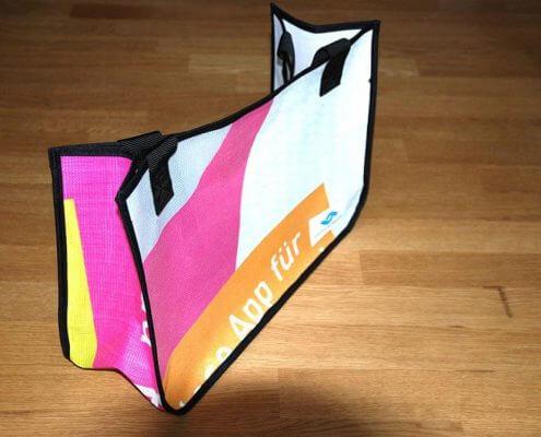 Upcycling Tasche aus wiederverwertetem Netzvinyl-Material der Stadtwerke Münster, die als Shopping Tasche genutzt werden kann.